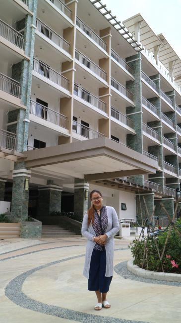 Mrs. Yvette Palaylay at the driveway of DMCI Homes Bristle Ridge's Outlook building.