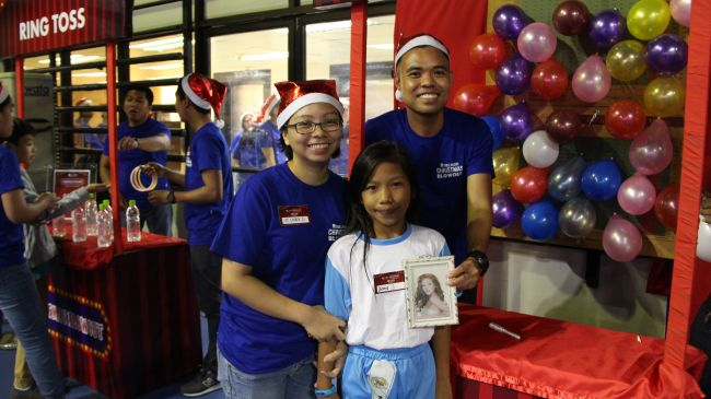 One of the beneficiaries gets her prize for a successful attempt in the Pop The Balloon game booth.